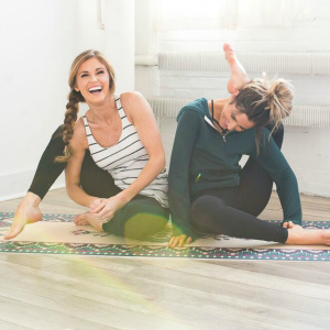 Two girls laughing and doing yoga