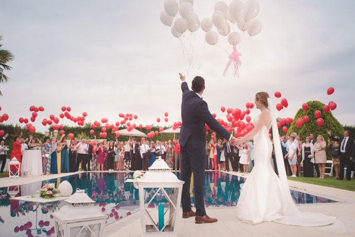 Wedding ceremony in front of a pool with balloons